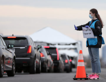 Philadelphia Medical Reserve Corps volunteer Emma Ewing, a sophomore at Temple University, directs cars at the city's coronavirus testing site next to Citizens Bank Park in South Philadelphia on Friday, March 20, 2020. (Tim Tai/The Philadelphia Inquirer)