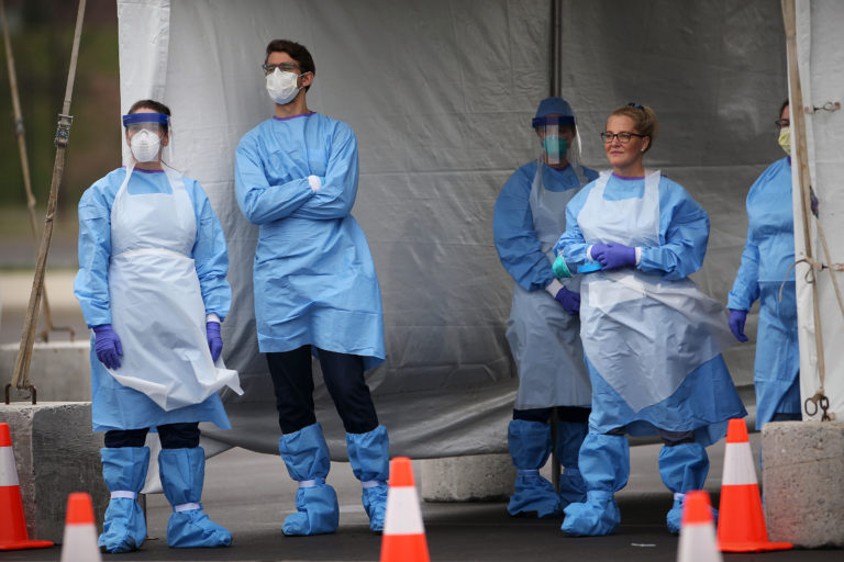 Medical workers wait for cars to pull up to the swabbing tent at the city's coronavirus testing site next to Citizens Bank Park in South Philadelphia on Friday, March 20, 2020. (The Philadelphia Inquirer)