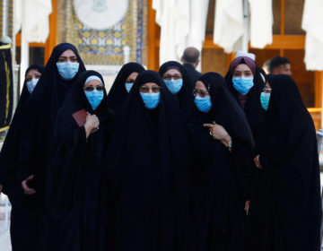 With the coronavirus spreading in dozens of countries, the World Health Organization officially declared the COVID-19 viral disease a pandemic Wednesday. Here, Muslim women wear protective face masks at the Imam Ali Shrine following an outbreak of the coronavirus in the city of Najaf, Iraq. (Alaa Al-Marjani/Reuters)
