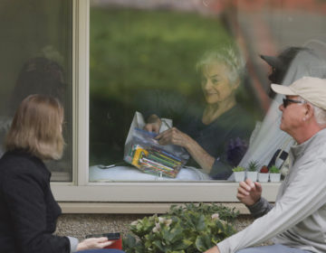 Judie Shape, center, who has tested positive for the new coronavirus, but isn't showing symptoms, opens a care package of art supplies from her daughter and her son-in-law, Tuesday, March 17, 2020, as they talk on the phone and look at each other through a window at the Life Care Center in Kirkland, Wash., near Seattle. (AP Photo/Ted S. Warren)