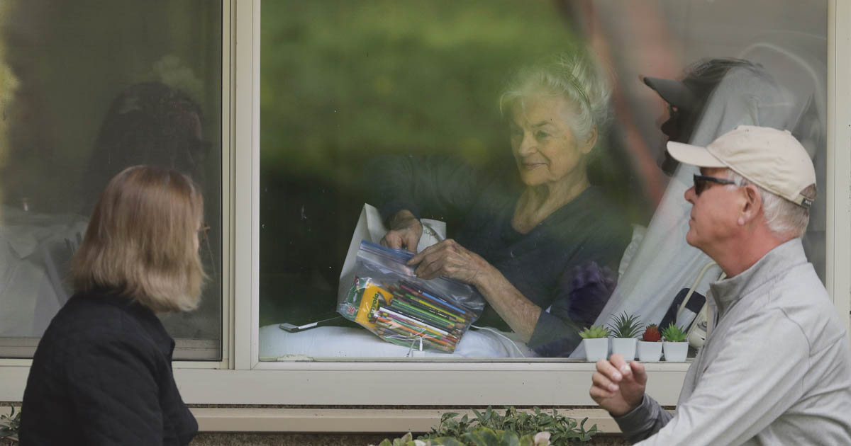 Judie Shape opens a care package of art supplies from her daughter Lori Spencer, left, and her son-in-law as they talk on the phone and look at each other through a window at the Life Care Center in Kirkland