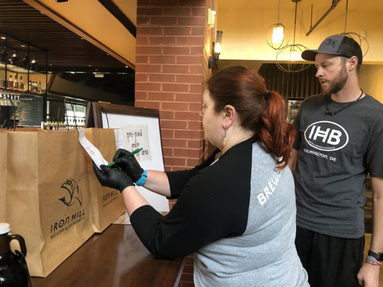 Moriah Guise and Dustin Mitchell check orders at Iron Hill Brewery. (Cris Barrish/WHYY)