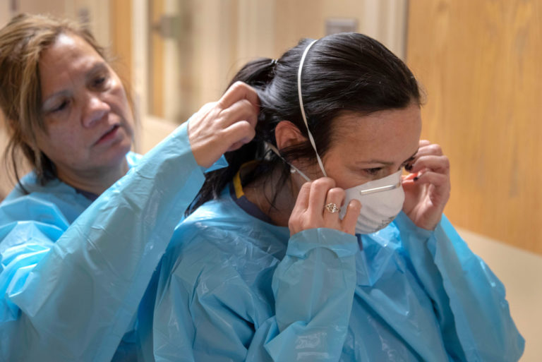 A nurse dons protective equipment with the assistance of colleagues at Holy Name Medical Center in Teaneck, New Jersey, March 19, 2020. (Jeff Rhode/Holy Name Medical Center)