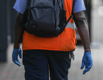 A man walks on Market Street in Wilmington, Del. wearing protective gloves on Friday, March 27, 2020. (Saquan Stimpson for WHYY)