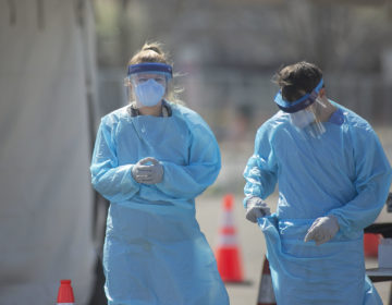 Healthcare workers at a new coronavirus testing site at the Cooper's Poynt Waterfront Park in Camden, NJ on Wednesday, April 1, 2020. Camden County officials open a new coronavirus testing site in Camden. (Miguel Martinez for WHYY)