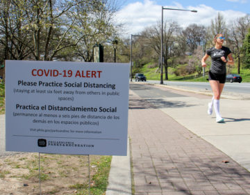 Signs posted along Philadelphia's Schuylkill River Trail caution users to keep six feet away from others to prevent the spread of COVID-19. (Emma Lee/WHYY)