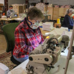 Luanne Albertson (center) sews masks at Eric and Christopher, LLC in Perkasie, Pa. (Emma Lee/WHYY)