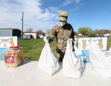 Delaware National Guard Private Kyeremen sets up a station for packaged food pick-up on Wednesday, April 8, 2020, at Frederick Lodge Manufactured Home Community in Townsend, Del. (Saquan Stimpson for WHYY)
