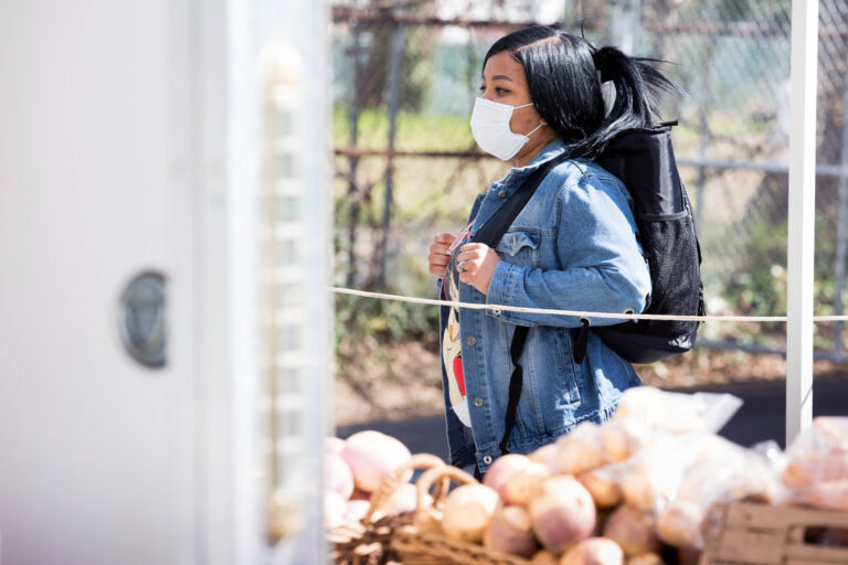 Njeri Harris shops for produce at the Landisdale Farm stand at Clark Park on April 11, 2020. Harris says that the lines enforcing social distancing are