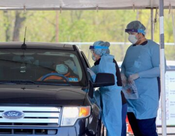 A medical technician performs a nasal swab on a patient at Camden's drive-through testing center at 2600 Mt. Ephraim Ave. (Emma Lee/WHYY)