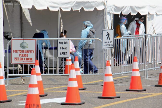 Medical personnel screen COVID-19 testing candidates at a site set up in the Motor Vehicle Commission parking lot in Camden, New Jersey. (Emma Lee/WHYY)