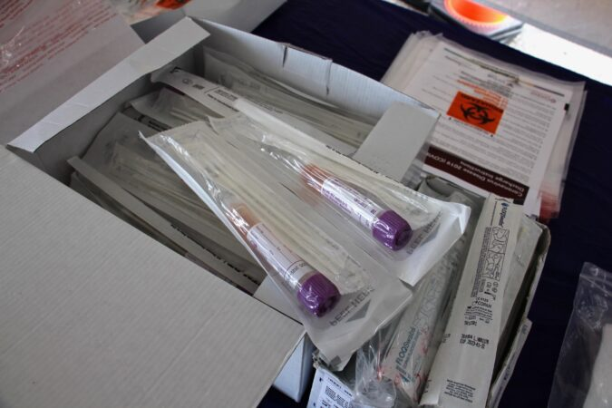 COVID-19 test kits are laid out on a table at the testing site at 2600 Mt. Ephraim Ave., Camden, New Jersey. (Emma Lee/WHYY)