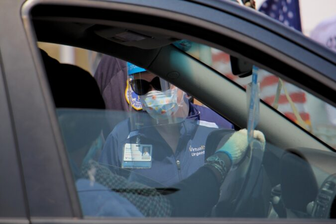 Nurse Practitioner Dodi Iannoco interviews drive-up testing candidates as they arrive at the testing site at 2600 Mt. Ephraim Ave. in Camden, New Jersey. (Emma Lee/WHYY)