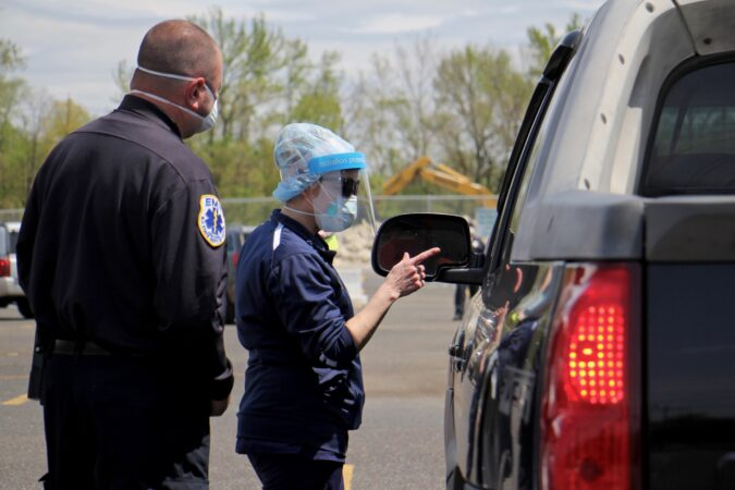 Nurse Practitioner Dodi Iannoco gives instructions to drive-up testing candidates as they arrive at the testing site at 2600 Mt. Ephraim Ave. in Camden, New Jersey. (Emma Lee/WHYY)