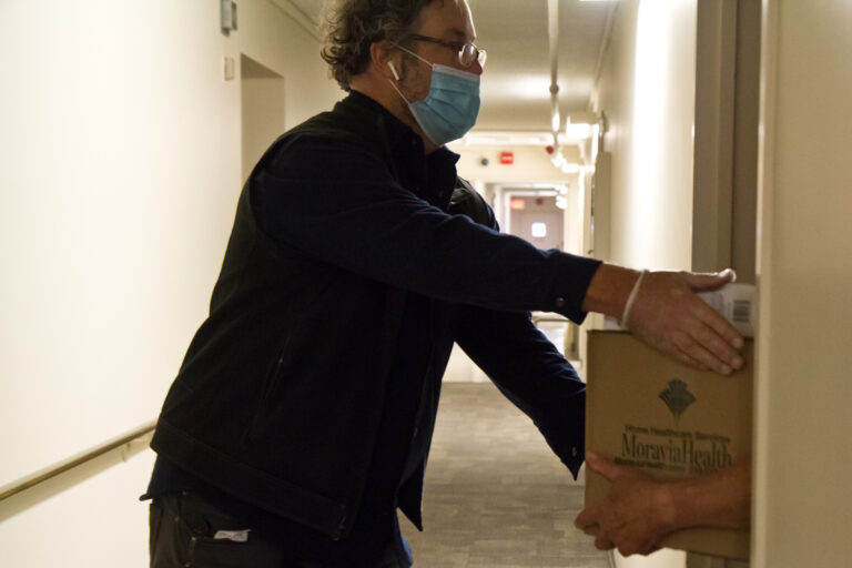 Volunteer Steve Huber drops off a box of food to a senior is public housing. (Kimberly Paynter/WHYY)