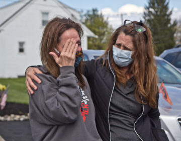 Tammy King (left) is comforted by her sister Michelle Rouco, both nurses, who were not allowed to see their father before he succumbed to COVID-19. (Kimberly Paynter/WHYY)