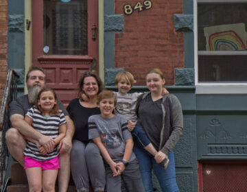 Wayne and Andrea Clark with their children Molly, 9, Caleb, 11, Roisin, 13, and Cianan, 6, on the steps of their home in Philadelphia. (Kimberly Paynter/WHYY)