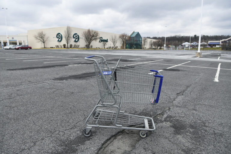 In this Tuesday, March 17, 2020, photo, a lone shopping cart sits in an empty parking lot near a shopping mall closed due to coronavirus concerns in Pottsville, Pa. (Jacqueline Dormer/Republican-Herald via AP)