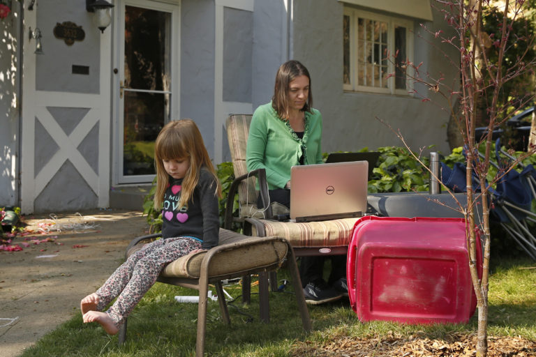 Alison Steffensen is joined by her daughter, Elin, 3, as she works at the home office she set up in the front yard of her home in Sacramento, Calif., Friday, March 20, 2020. (AP Photo/Rich Pedroncelli)