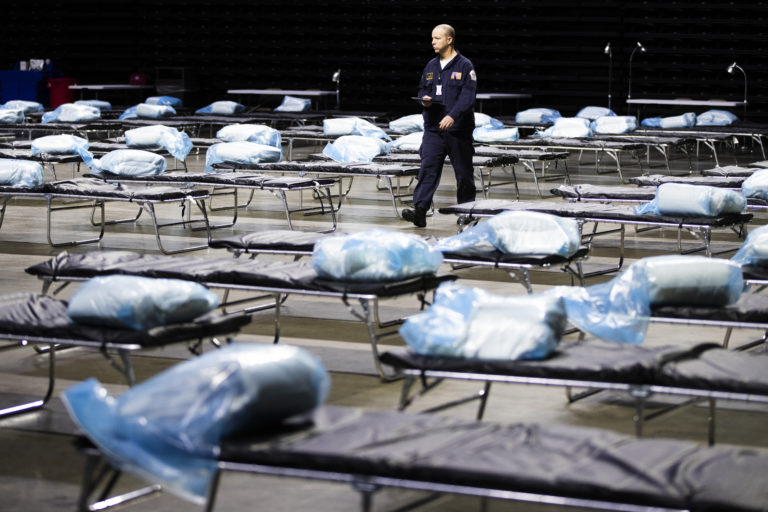 Pennsylvania Task Force 1 member Greg Rogalski walks amongst the beds of a Federal Medical Station for hospital surge capacity set up at Temple University's Liacouras Center in Philadelphia, Monday, March 30, 2020. (AP Photo/Matt Rourke)