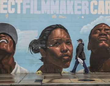 A woman wearing a surgical mask makes her way past a mural on the west side of the Save-A-Lot store at 22nd and Lehigh. (Michael Bryant/The Philadelphia Inquirer via AP)