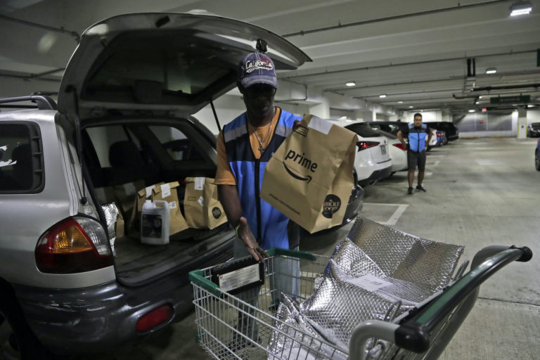 Samuel Diaz, a delivery worker for Amazon Prime, loads his vehicle with groceries from Whole Foods, Tuesday, March 31, 2020, in Miami, during the coronavirus pandemic. (Lynne Sladky/AP Photo)