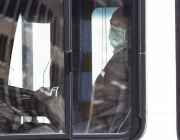A Southeastern Pennsylvania Transportation Authority bus driver wears a protective mask as he drives through in Philadelphia, Wednesday, April 1, 2020. (AP Photo/Matt Rourke)