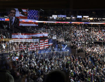 The stage is reflected on a glass window on the suite level at Wells Fargo Arena as Timmy Kelly sings the national anthem before the start of the second day session of the Democratic National Convention in Philadelphia, in 2016.  (John Locher/AP Photo, File)