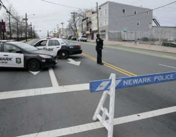 A police officer stands at an intersection on the border between Irvington and Newark, N.J., Friday, April 3, 2020. (Seth Wenig/AP Photo)