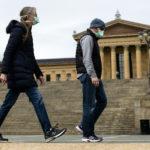 A couple in protective masks walk past the Philadelphia Museum of Art in Philadelphia, Friday, April 3, 2020. (Matt Rourke/AP Photo)