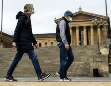 A couple in protective masks walk past the Philadelphia Museum of Art in Philadelphia, Friday, April 3, 2020. The museum has temporarily closed due to the COVID-19 pandemic.  (AP Photo/Matt Rourke)