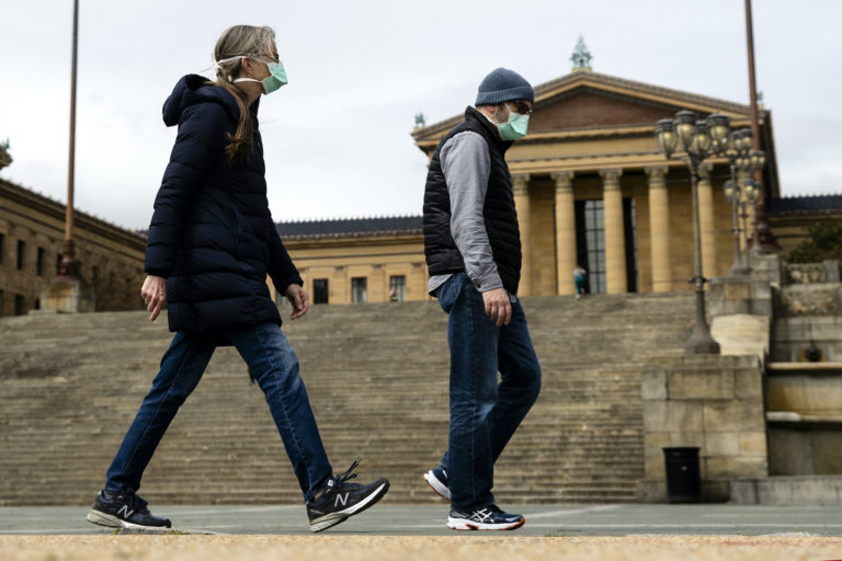 A couple in protective masks walk past the Philadelphia Museum of Art in Philadelphia, Friday, April 3, 2020. (Matt Rourke/AP Photo)
