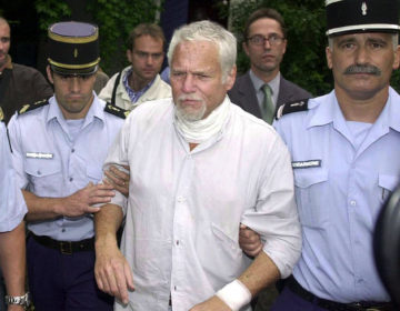 In this Thursday July 19, 2001 file photo, U.S. fugitive Ira Einhorn is taken away by French police in Champagne-Mouton, central France to be extradited to the United States. (Bob Edme/AP Photo)