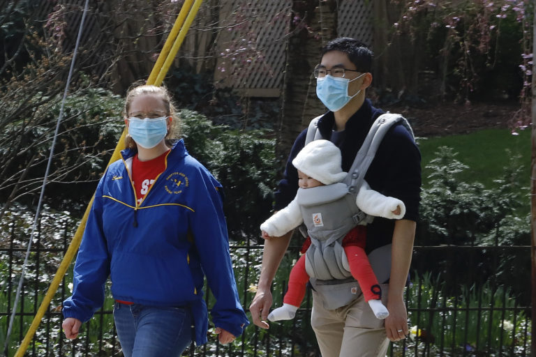 A couple out for walk wear protective masks on a warm afternoon in Pittsburgh, Sunday, April 5, 2020. (AP Photo/Gene J. Puskar)