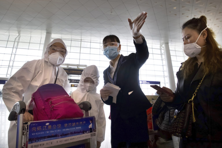 A worker directs travelers wearing face masks and suits to protect against the spread of coronavirus at Wuhan Tianhe International Airport in Wuhan in central China's Hubei Province, Wednesday, April 8, 2020. Within hours of China lifting an 11-week lockdown on the central city of Wuhan early Wednesday, tens of thousands people had left the city by train and plane alone, according to local media reports. (AP Photo/Ng Han Guan)
