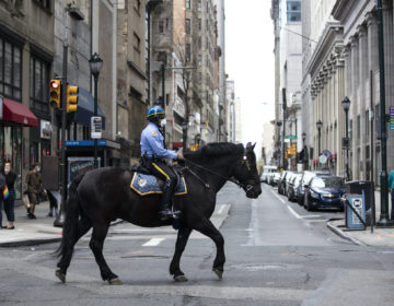 A mounted officer patrols while wearing a face mask to protect against the spread of new coronavirus, in Philadelphia, Wednesday, April 8, 2020. (AP Photo/Matt Rourke)