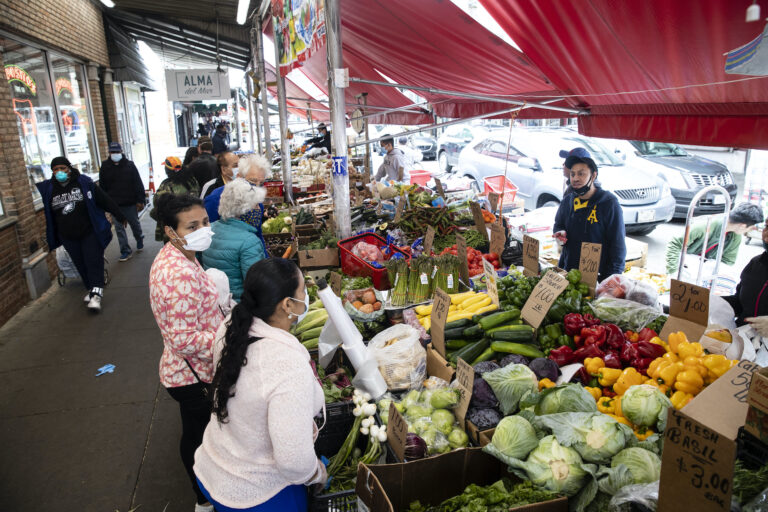 Customers wearing face coverings to protect against the spread of the coronavirus, shop at a produce stand on South 9th Street in the Italian Market neighborhood of Philadelphia, Thursday, April 9, 2020. (AP Photo/Matt Rourke)