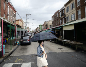 A shopper wearing a face mask to protect against the spread of the new coronavirus crosses South 9th Street in the Italian Market neighborhood of Philadelphia, Thursday, April 9, 2020. (AP Photo/Matt Rourke)