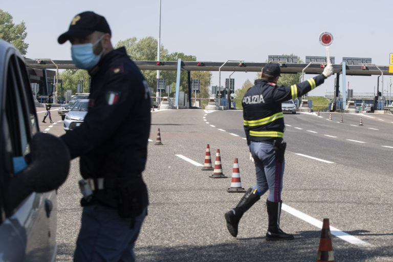 Police officers stop cars at the Melegnano highway barrier entrance, near Milan, Italy, Saturday, April 11, 2020. (Luca Bruno/AP Photo)