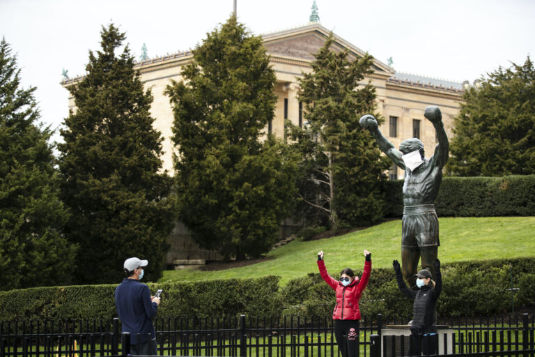 People wearing a protective face masks as a precaution against the coronavirus take photos with the Rocky statue outfitted with mock surgical face mask at the Philadelphia Art Museum in Philadelphia, Tuesday, April 14, 2020. (AP Photo/Matt Rourke)