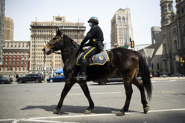 A mounted police officer patrols while wearing a protective face mask as a precaution against the coronavirus in Philadelphia, Friday, April 17, 2020. (AP Photo/Matt Rourke)
