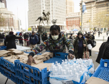 Volunteer Diamon Logan with Broad Street Ministry distributes food as part of a new initiative called Step Up to the Plate, outside City Hall in Philadelphia, Friday, April 17, 2020. The program aims to help those with food insecurity and is a partnership of Broad Street Ministry, Prevention Point Philadelphia, and Project HOME, with the City of Philadelphia. (AP Photo/Matt Rourke)