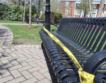 Police tape covers park benches in Rutherford, New Jersey, to enforce social distancing during the coronavirus pandemic on Sunday, April 19, 2020. (AP Photo/Ted Shaffrey)