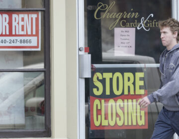 Man walks past closed business amid coronavirus pandemic.