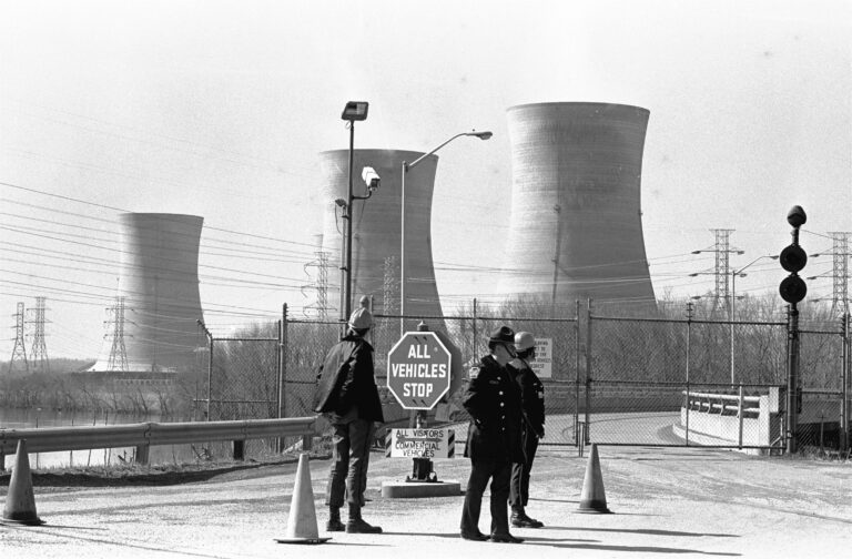 FILE - In this Wednesday, March 28, 1979 file photo, a Pennsylvania state police officer and plant security guards stand outside the closed front gate to the Three Mile Island nuclear power plant near Harrisburg, Pa. after the plant was shut down following a partial meltdown. (AP Photo/Paul Vathis)