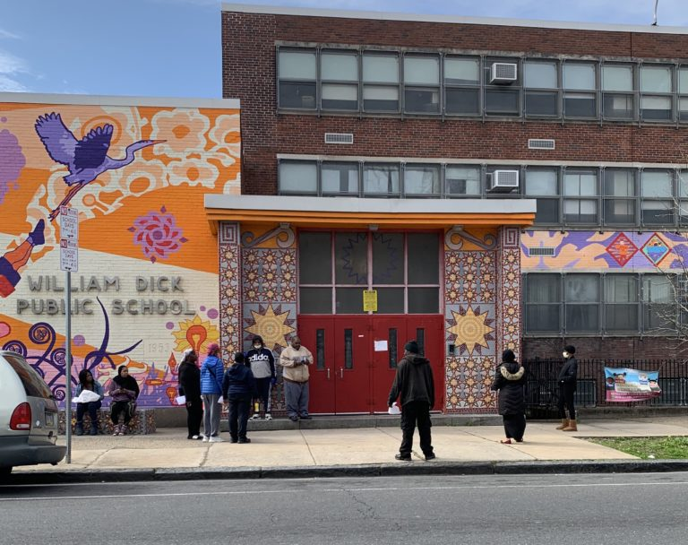 People outside William Dick Elementary School in North Philadelphia wait to pick up Chromebooks.