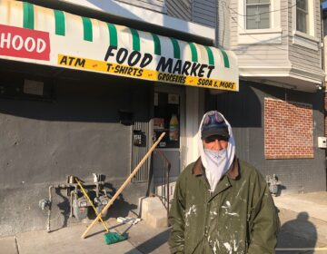 Melvin Santiago wear his makeshift mask Friday morning while doing some renovation and repair work at a store on Fourth Street and Delamore Place in Wilmington. (Cris Barrish/WHYY)