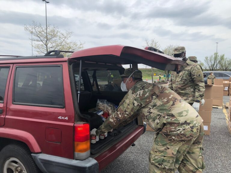Brian Turner of the Delaware National Guard places food in a trunk during Monday's giveaway. (Cris Barrish/WHYY)