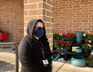 Miriam Casillas stands guard outside the Acme in Pike Creek, making sure shoppers are wearing a mask. (Cris Barrish/WHYY)