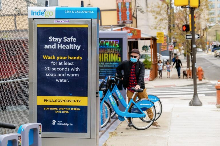 A rider stands next to an Indego station. (Credit: Indego/City of Philadelphia)